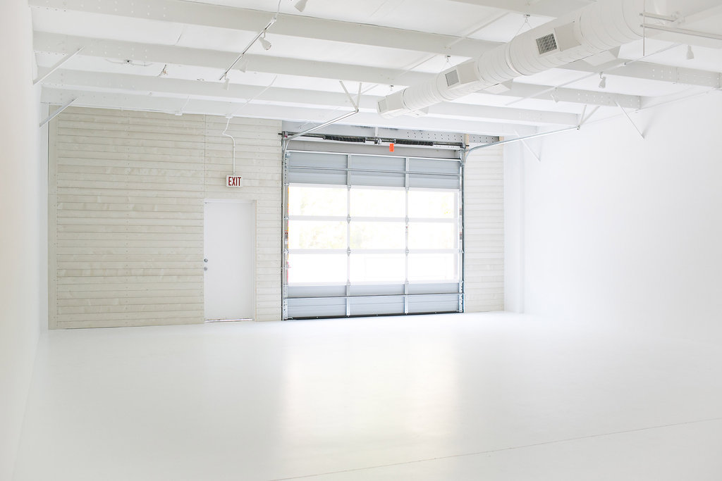 Studio open white canvas space, front right angle, with garage door